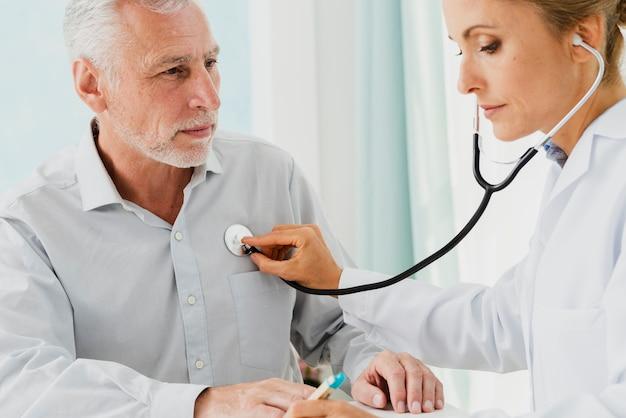 Doktor, der anmerkungen beim auskultieren schreibt
