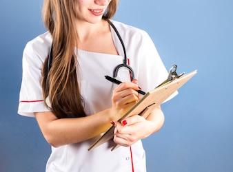 Doktor, der ärztliche Verordnung in Klemmbrett schreibt