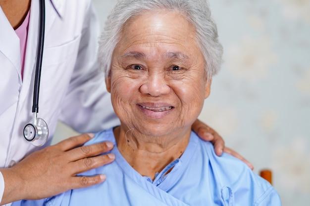 Doktor, der asiatischen älteren frauenpatienten mit liebe berührt.