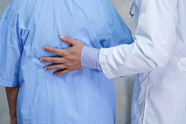 Doktor, der asiatischen älteren fraupatienten mit liebe und fürsorge berührt.