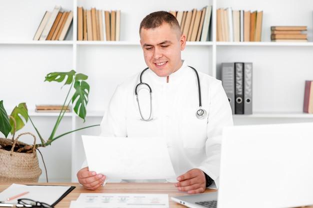 Doktor, der auf schreibtisch sitzt und auf einem blatt schaut