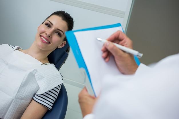 Doktor, der auf zwischenablage schreibt, während patient auf zahnbett liegt