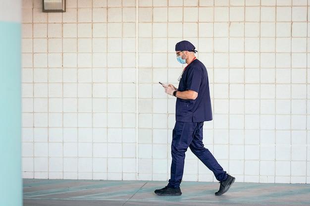 Doktor, der außerhalb des krankenhauses mit smartphone geht