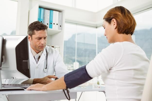 Doktor, der blutdruck der frau im ärztlichen dienst überprüft