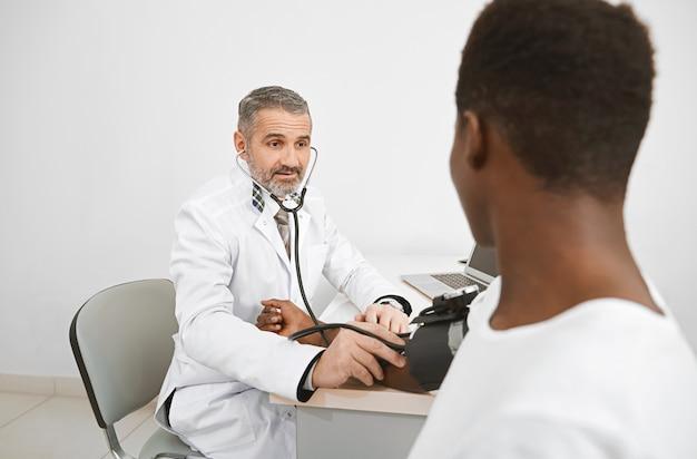 Doktor, der blutdruck mit blutdruckmessgerät misst.