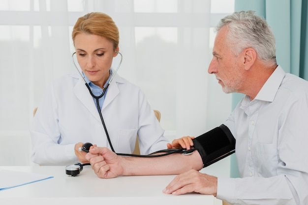 Doktor, der blutdruck überprüft