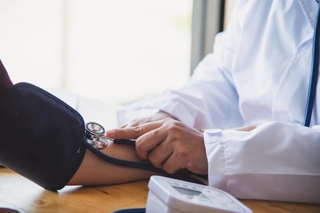 Doktor, der blutdruck von ihrem patienten misst