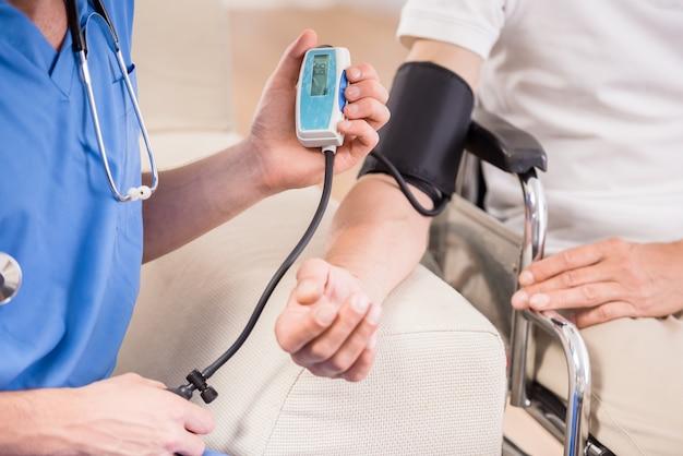 Doktor, der blutdruck zum älteren patienten misst.