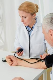 Doktor, der blutdruckmanschette aufbläst