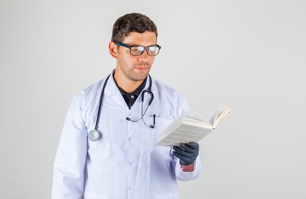 Doktor, der buch im medizinischen weißen gewand liest