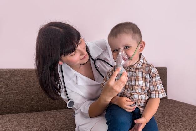 Doktor, der dem kleinen jungen mit verneblermaske hilft