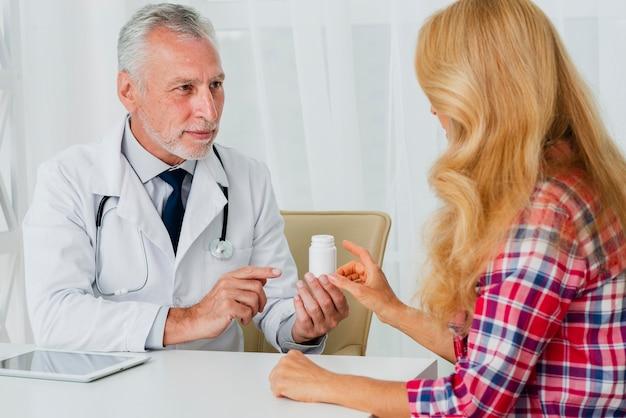Doktor, der dem patienten medikation übergibt