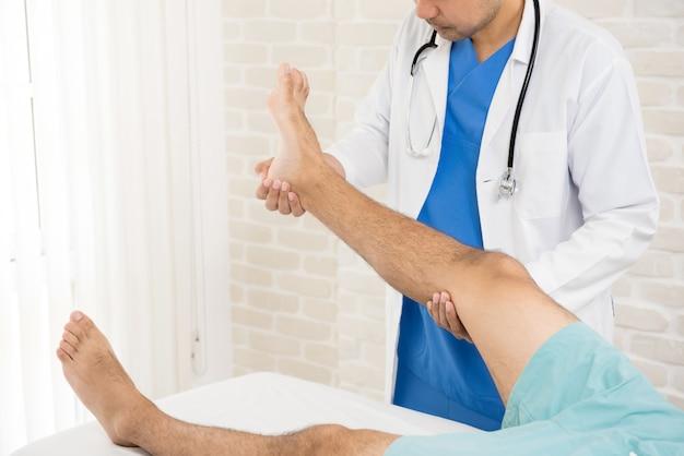 Doktor, der dem patienten mit gebrochenem bein behandlung gibt