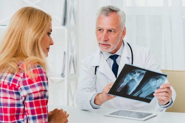 Doktor, der dem patienten röntgenstrahl zeigt