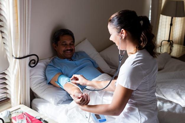 Doktor, der den blutdruck der älteren frau im schlafzimmer prüft