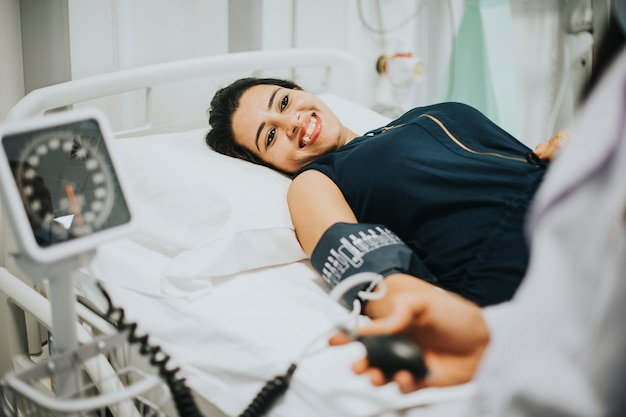 Doktor, der den blutdruck eines patienten überprüft
