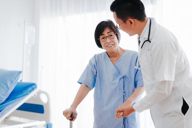 Doktor, der der älteren frau geht mit einem stock hilft