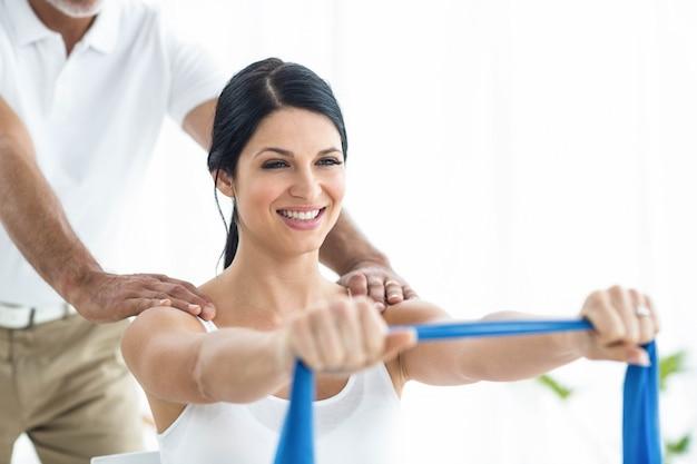 Doktor, der der schwangeren frau auf übungsball physiotherapie überprüft und gibt