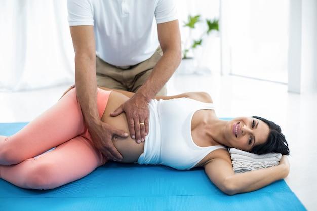Doktor, der der schwangeren frau physiotherapie überprüft und gibt