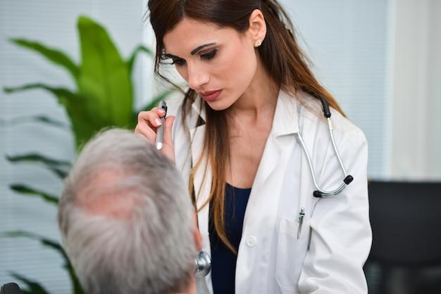 Doktor, der die augen eines patienten besucht