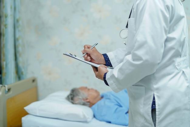 Doktor, der die diagnose auf klemmbrett im krankenhaus notiert.