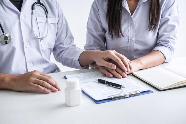 Doktor, der die hände des patienten hält, um zu ermutigen und mit dem zujubeln und der unterstützung des patienten zu sprechen