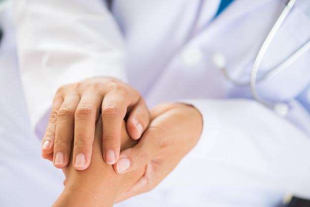 Doktor, der die hand des patienten hält. medizin und gesundheits-konzept