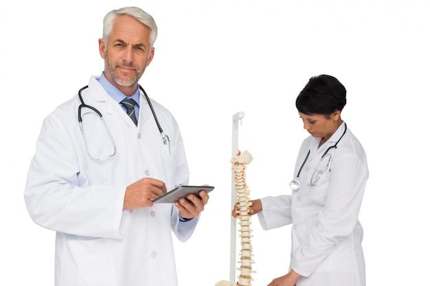 Doktor, der digitale tabelle mit kollegen durch skeleton modell hält