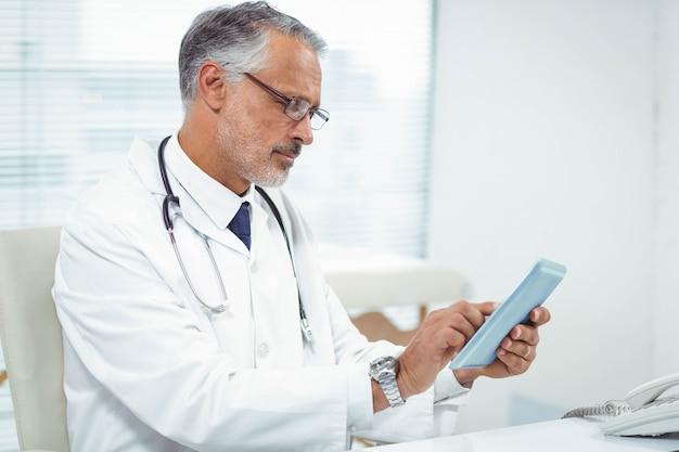 Doktor, der digitale tablette an der klinik verwendet