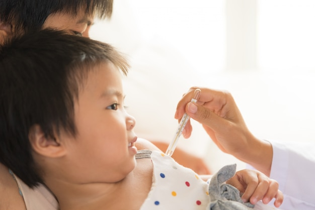 Doktor, der digitalen thermometer zur messenden temperatur ihres kranken kindes hält