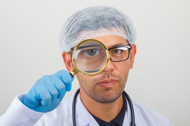 Doktor, der durch lupe im weißen kittel und im hut schaut