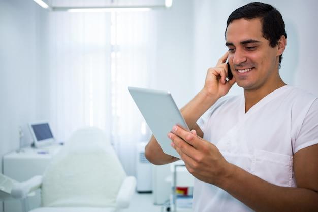 Doktor, der ein digitales tablett hält, während auf handy spricht