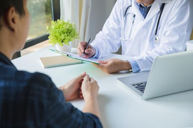 Doktor, der ein klemmbrett verwendet, um eine krankengeschichte der medikation und des patienten eines jungen mannes auszufüllen, welche die ergebnisse einer körperlichen untersuchung in einer klinik besprechen