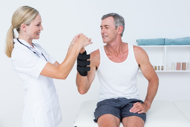 Doktor, der ein mannhandgelenk überprüft
