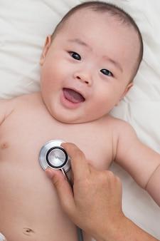 Doktor, der ein stethoskop verwendet, um auf den kasten des babys zu hören