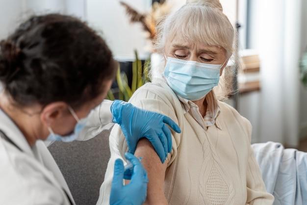 Doktor, der eine ältere frau impft