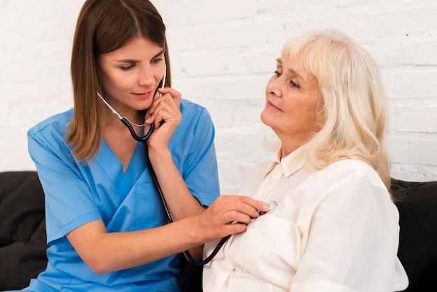 Doktor, der eine alte frau mit ihrem stethoskop überprüft