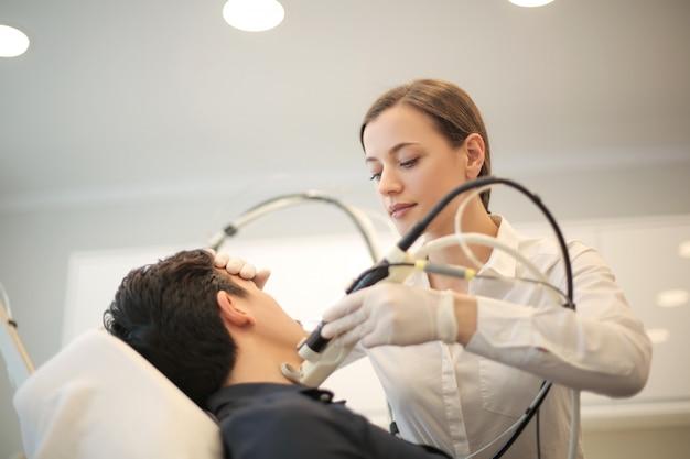 Doktor, der eine dermatologiebehandlung auf einem patienten tut