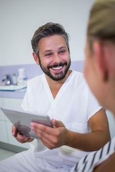 Doktor, der eine digitale tablette hält, während er mit patient spricht