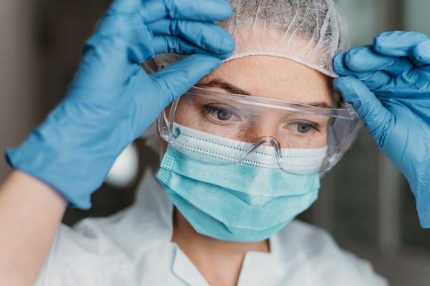 Doktor, der eine gesichtsmaske und eine schutzbrille trägt