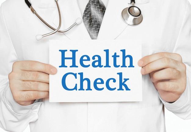 Doktor, der eine karte mit gesundheitscheck, medizinisches konzept hält