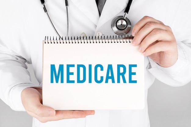 Doktor, der eine karte mit medicare, medizinisches konzept hält
