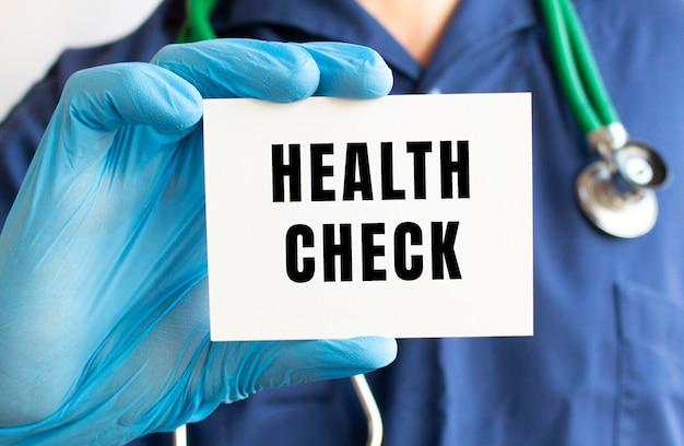 Doktor, der eine karte mit text gesundheitsprüfung hält. medizinisches konzept.