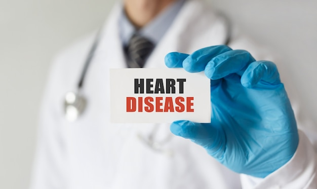 Doktor, der eine karte mit text herzkrankheit, medizinisches konzept hält