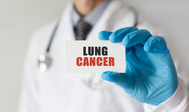 Doktor, der eine karte mit text lungenkrebs, medizinisches konzept hält