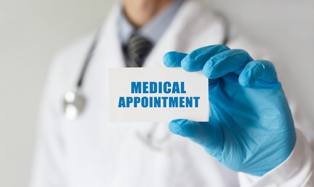 Doktor, der eine karte mit text medizinischer termin, medizinisches konzept hält