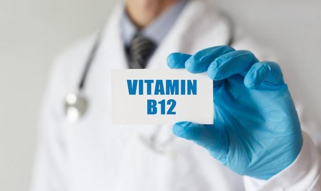 Doktor, der eine karte mit textvitamin b12, medizinisches konzept hält