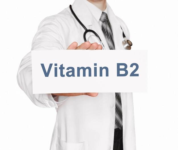 Doktor, der eine karte mit vitamin b2, medizinisches konzept hält