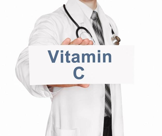Doktor, der eine karte mit vitamin c, medizinisches konzept hält
