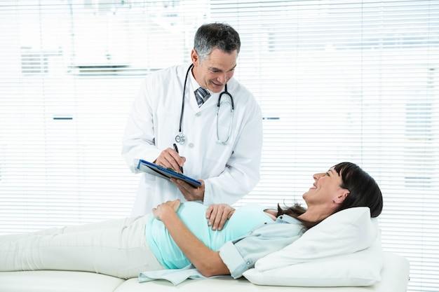 Doktor, der eine schwangere frau im krankenhaus überprüft